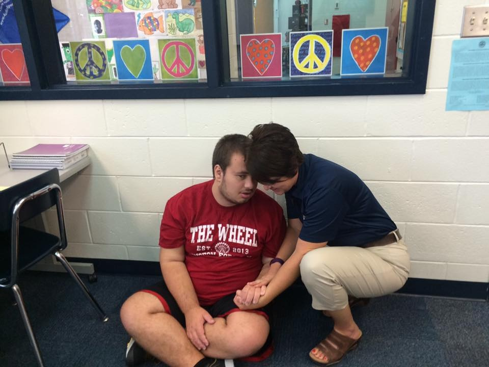 Photo of a young adult boy sitting cross leg on a classroom floor, with an aid talking kindly to him
