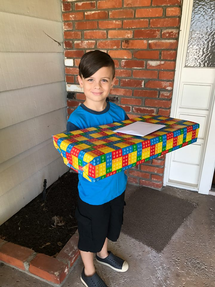 Photo of a child, boy, standing in front of a home folding a present